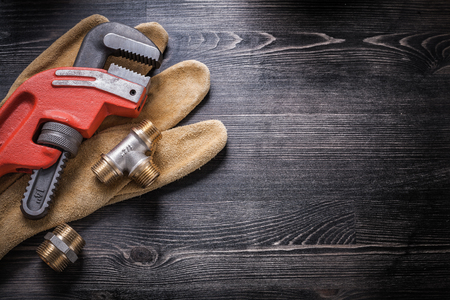 household fixture: Monkey wrench pipe fittings safety gloves on wooden board.