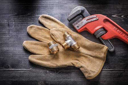 Pipe wrench plumbing fixtures safety gloves on wooden board. Stock Photo