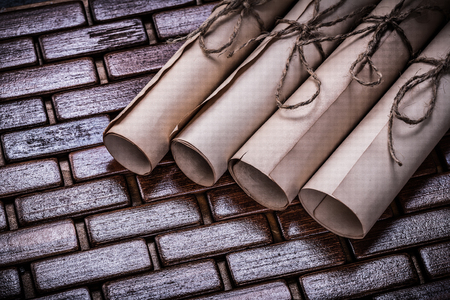 matting: Pile of vintage parchment rolls on wicker wooden matting.