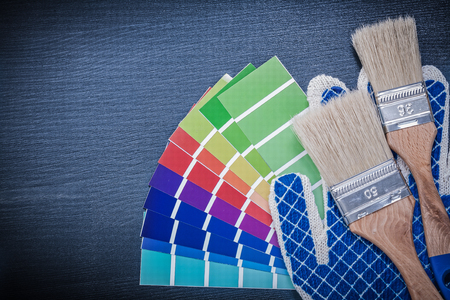 repaint: Paintbrushes pantone fan safety gloves on wooden board. Stock Photo