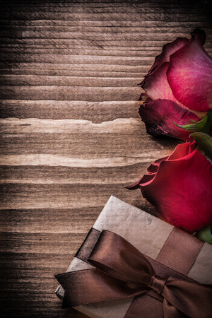 expanded: Natural expanded roses present box on wood board holidays concept. Stock Photo