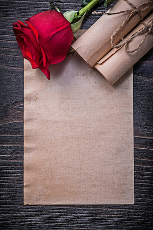 corded: Vintage corded paper rolls red expanded rose on wooden board.