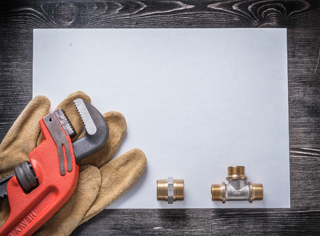 pipe wrench: Pipe wrench brass plumbing fittings leather safety gloves blank paper. Stock Photo