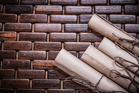 matting: Rolled vintage documents on wicker wooden matting.
