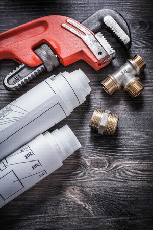 fixtures: Pipe wrench copper plumbing fixtures rolled up construction plans.