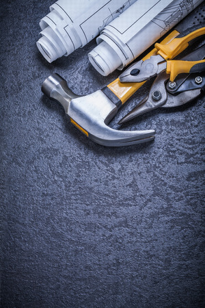 snips: Rolled blueprints tin snips pliers claw hammer on black background.