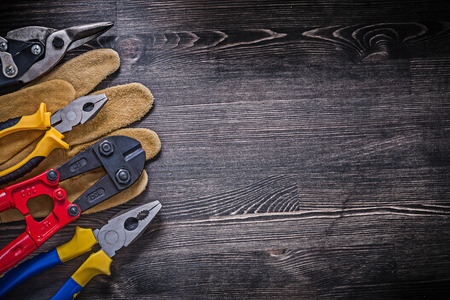 wire cutter: Safety glove steel wire cutter pliers on wooden background copyspace. Stock Photo