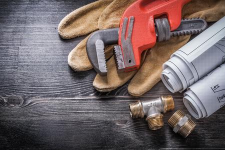 fixtures: Monkey wrench copper plumbing fixtures safety gloves blueprint rolls.