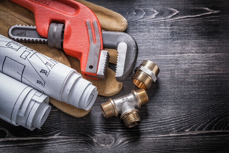 household fixture: Pipe wrench brass plumbing fittings safety gloves blueprint rolls.
