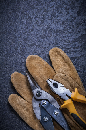 snips: Sharp tin snips gripping tongs leather safety glove construction concept.