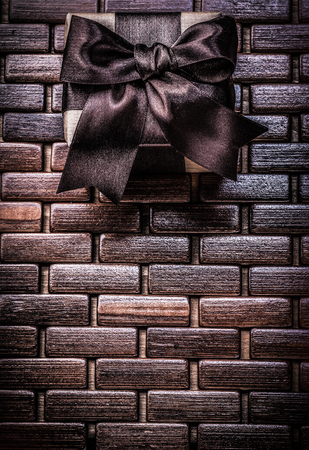 matting: Packed gift box with brown ribbon on wicker wooden matting.