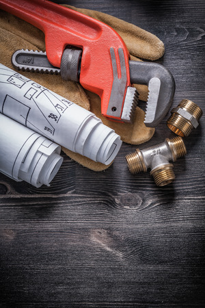 pipe wrench: Pipe wrench brass plumbing fittings protective gloves blueprint rolls.
