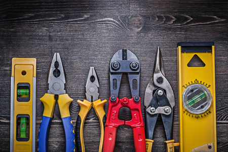 construction level: Tin snips steel cutter pliers construction level on wooden board.