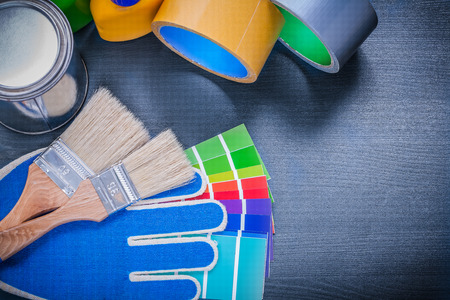 Paint containers color sampler safety gloves paintbrushes adhesive tape.