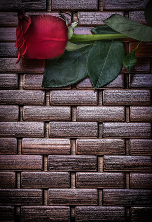 matting: Red rose on wicker wooden matting copy space.
