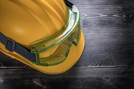 protective glasses: Protective glasses hard hat on wooden board construction concept.