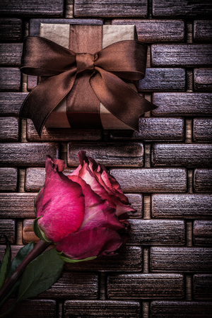 scented: Red scented rose present box on wicker wooden place mat.