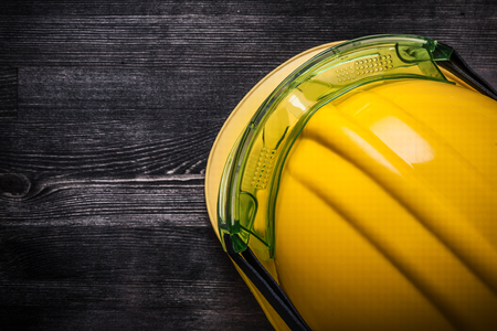 protective glasses: Protective glasses building helmet on wooden board construction concept.