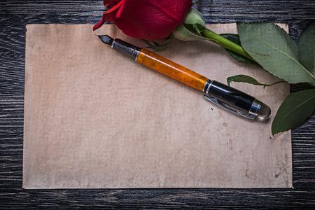 felicitaciones cumplea�os: Papel de la vendimia roja expandi� pluma capullo de rosa sobre tabla de madera. Foto de archivo