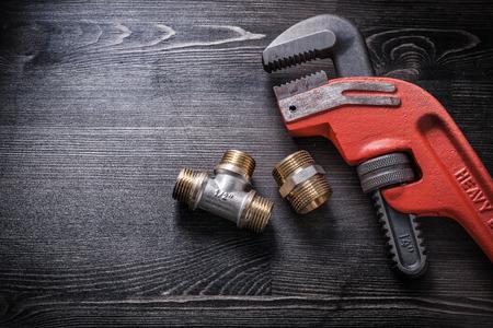 household fixture: Monkey wrench plumbing fittings on wooden board.