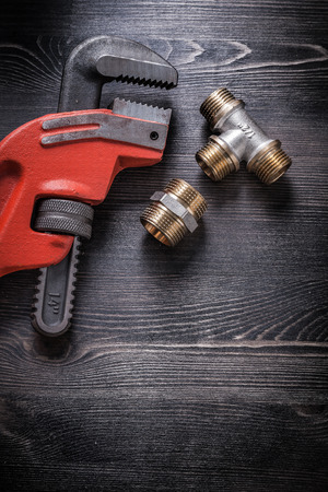 household fixture: Pipe wrench brass plumbing fittings on wooden board.