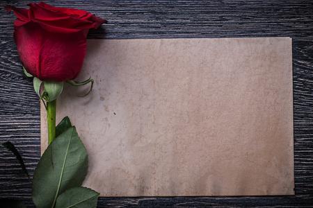birthday greetings: Vintage paper red scented rosebud on wood board.