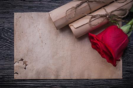 birthday greetings: Papel de la vendimia rueda capullo de rosa perfumada de color rojo sobre fondo de madera. Foto de archivo