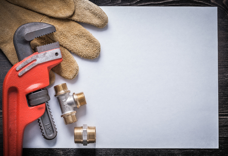 fittings: Monkey wrench brass plumbing fittings leather safety gloves clean paper. Stock Photo