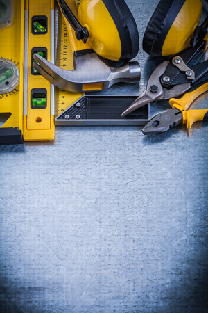 toolset: Try square construction level claw hammer pliers tin snips earmuffs. Stock Photo