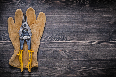 snips: Leather safety glove tin snips on wood board construction concept. Stock Photo