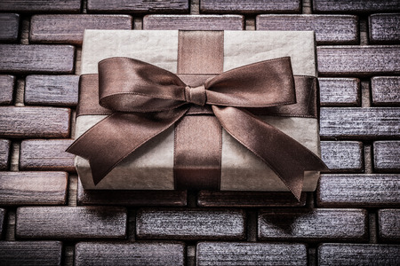 giftbox: Wrapped giftbox with ribbon on wooden wicker matting holidays concept.