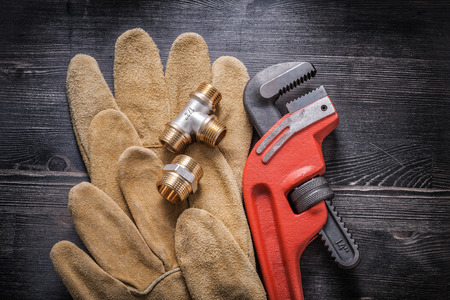 household fixture: Monkey wrench plumbing fittings leather protective gloves on wooden board.