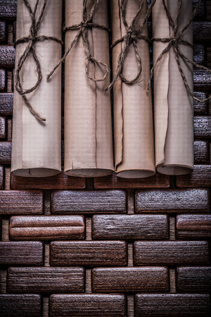 matting: Pile of vintage paper scrolls on wicker wooden matting.