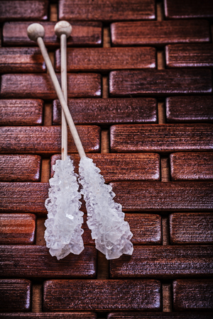 matting: Sweet sugar sticks on wooden matting.