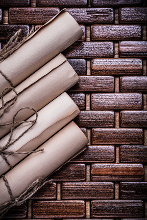 matting: Rolled vintage documents with string on wicker wooden matting.