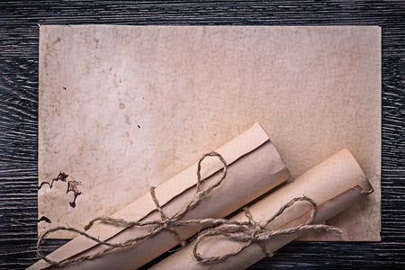 writing desk: Vintage rolled corded paper on wooden background. Stock Photo