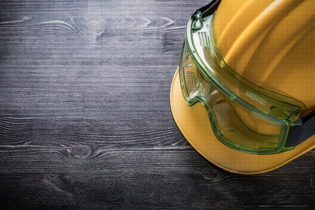 Safety glasses building helmet on wooden board construction concept. Standard-Bild