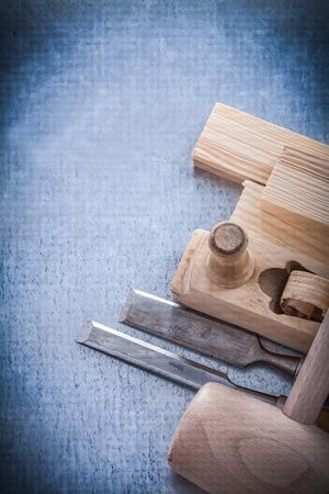 stud: Wooden shaving plane hammer stud flat chisels on metallic background.