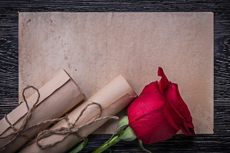 corded: Vintage paper scrolls red scented rose on wooden background.