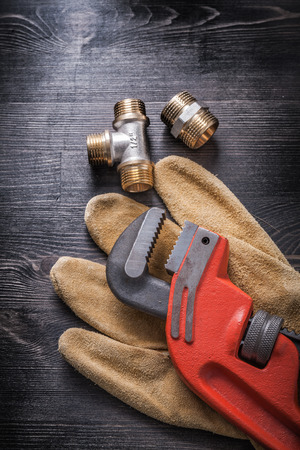 protective gloves: Monkey wrench brass plumbing fittings leather protective gloves construction concept.