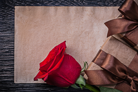 expanded: Vintage paper red expanded rose wrapped giftboxes on wooden board. Stock Photo