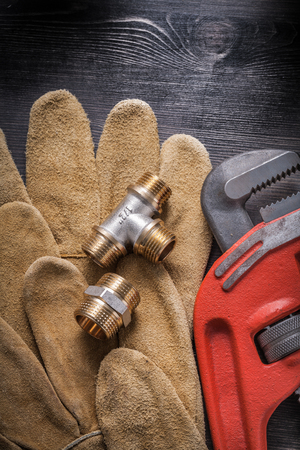 pipe wrench: Pipe wrench plumbing fittings leather protective gloves on wooden board.