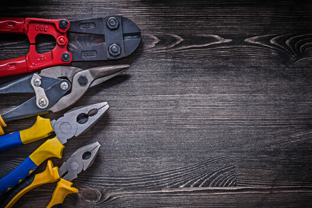 wire cutter: Stainless wire steel cutter pliers on wooden board copy space.