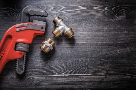 pipe wrench: Pipe wrench plumbing fittings on wooden board.