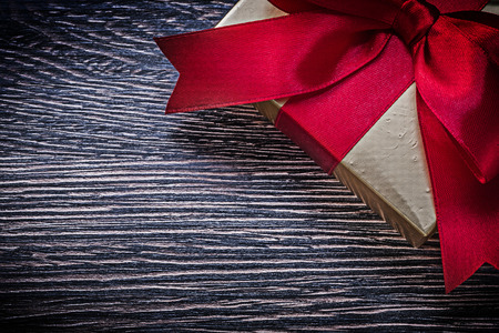 wrapped gift: Tied wrapped gift box on wooden board holiday concept.
