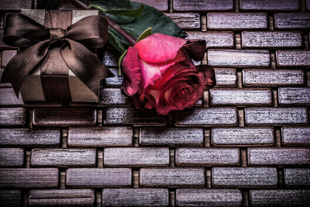 matting: Red expanded rose present box on wicker wooden matting. Stock Photo