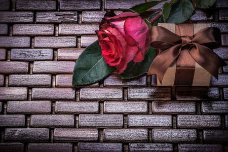 giftbox: Red rose giftbox on wicker wooden place mat.