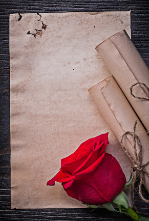 corded: Vintage corded paper rolls red rose on wooden board. Stock Photo