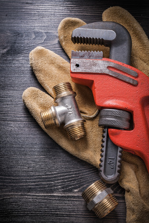 protective gloves: Monkey wrench plumbing fixtures protective gloves on wooden board.
