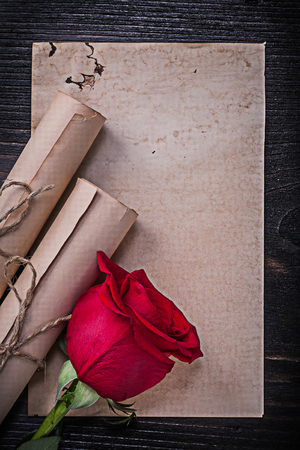 corded: Vintage corded paper rolls red natural rose on wooden board.